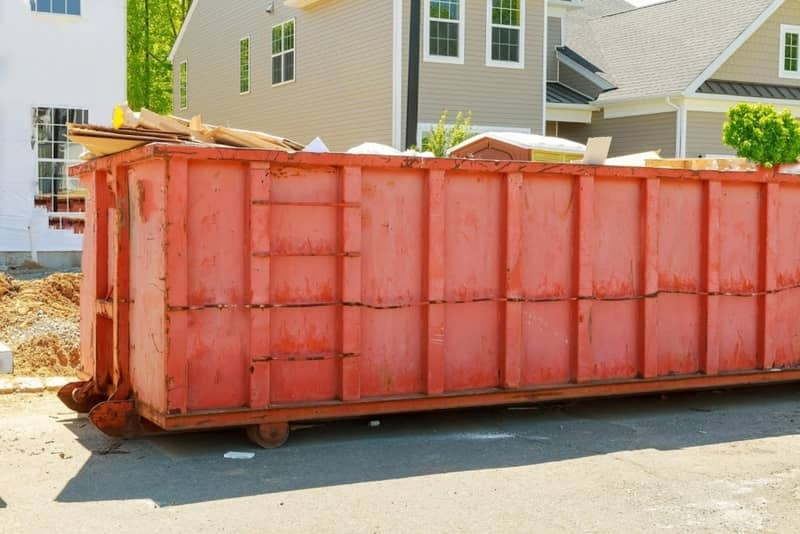 Red commercial dumpster deployed outside at a construction site in Walker St Augusta GA.
