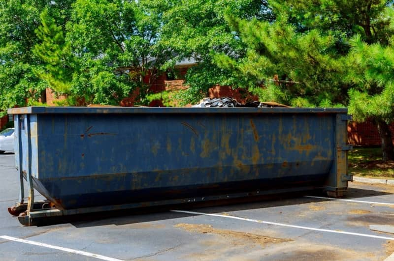 Blue construction dumpster at a home near the Terrace Manor Elementary School area on the parking lot collecting construction waste.