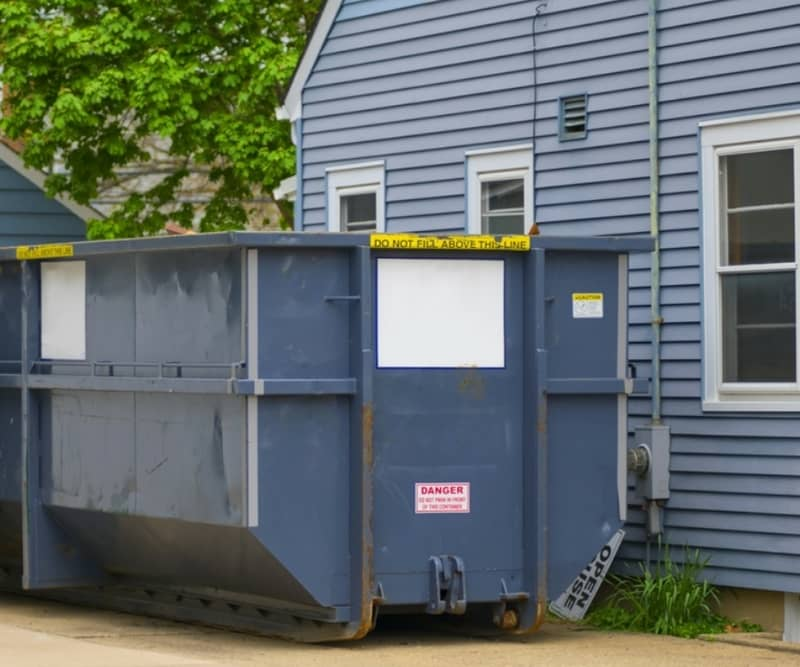 A residential dumpster delivered next to a house for a family near First Mount Hermon Baptist Church in Augusta.