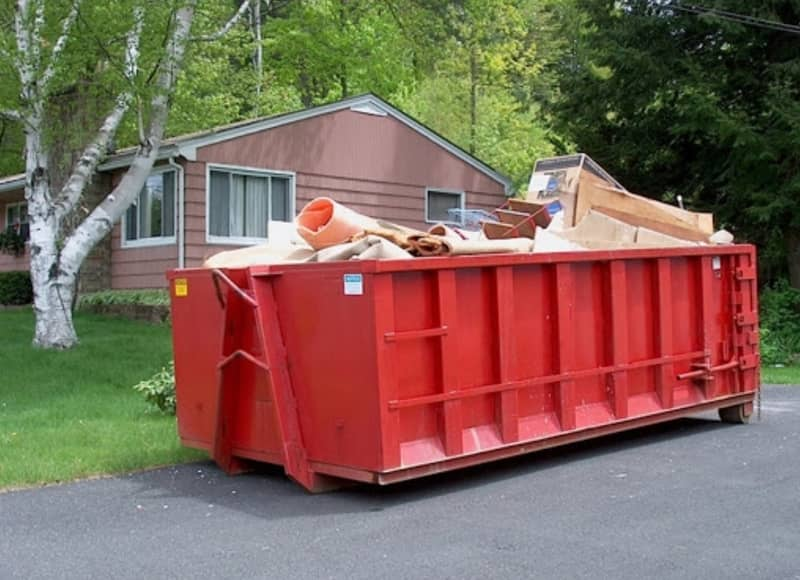 A red 20 yard residential dumpster filled with household waste in East Augusta GA area.