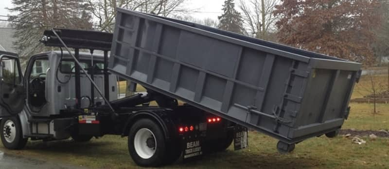 A residential dumpster is rolled off from a truck for a residential place near Bicentennial Chapel in Augusta GA area.